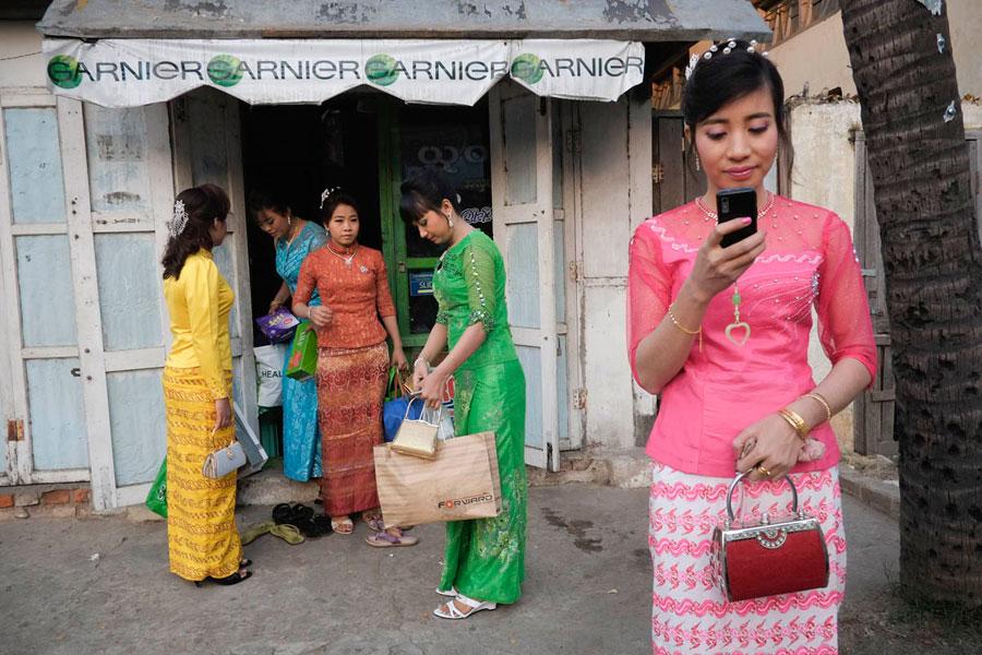 Myanmar college graduates leaving a beauty salon