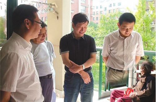 "Offbeat China explains why the Anhui government produced the above photoshop image in which four giant officials were surrounding a tiny elderly woman: due to limited space at the lady's home, it's impossible to put everybody in the frame so they ""had to put together two separate pictures."""