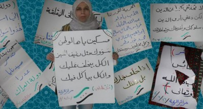 Suad Nofal, surrounded by her banners. Source: Syria Untold