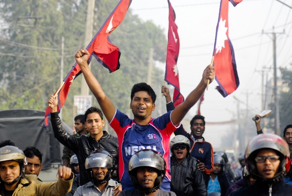 Young Nepali cricket fans raise the national flag to celebrate their surprise qualification for the Twenty20 World Cup final in 2014. Image by Manish Paudel, Copyright Demotix (28/11/2013)