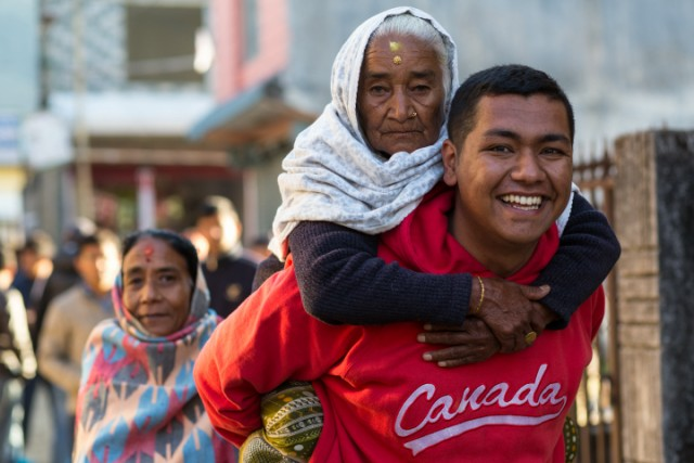 An elderly woman being carried by her grandson from a voting centre after casting her vote in the second Constitution Assembly election. Photo by Nabin Baral. Copyright Demotix (19/11/2013)