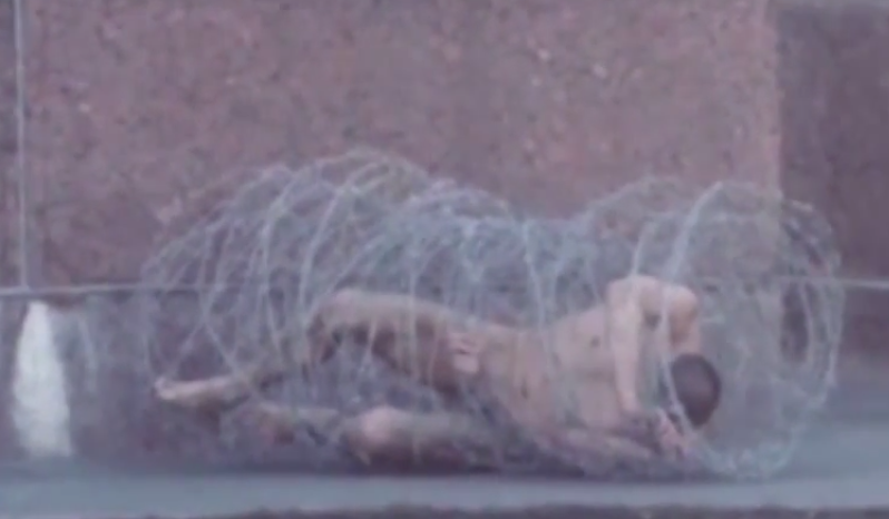Pavlensky's barbed wire protest, 2 May 2013, St. Petersburg, Russia, YouTube capture.