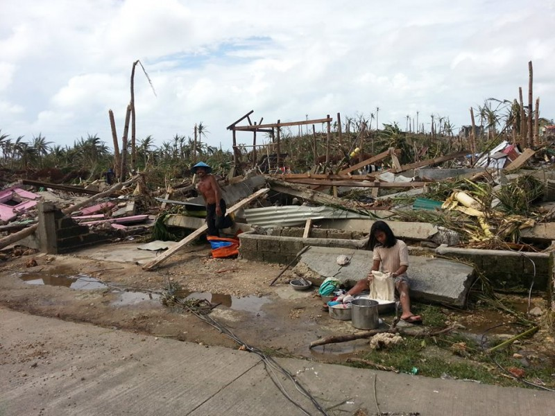 A woman washing clothes amid the debris after the storm. Photo by David Yu Santos, Facebook