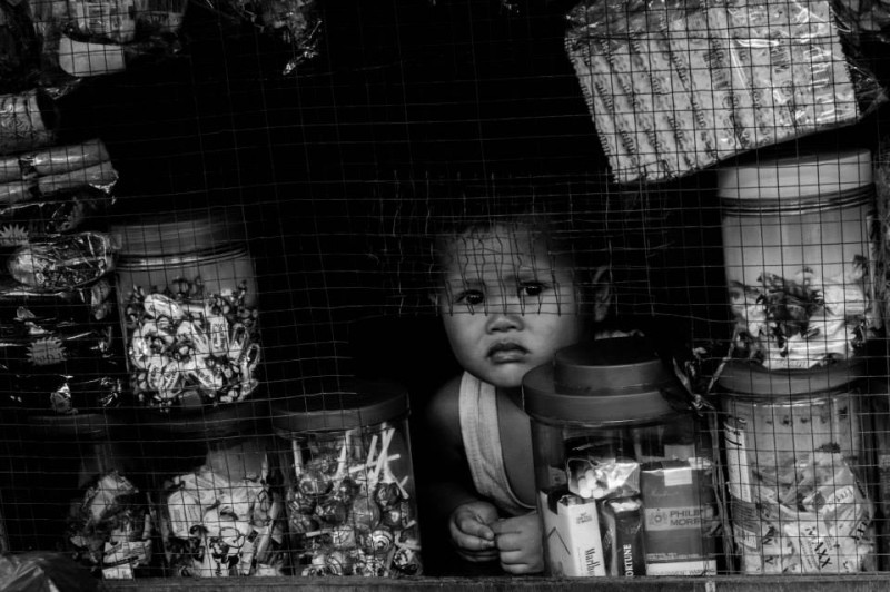 A child peers through a small window of a thrift store which sells candies and cigarettes