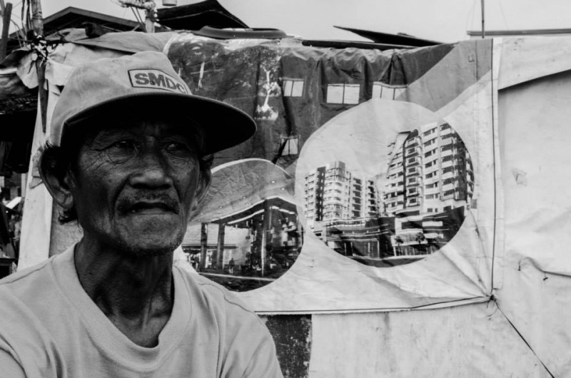 A man wearing an SM cap. SM is owned by the Philippines' richest businessman. Behind the man is a tarpaulin displaying some construction projects