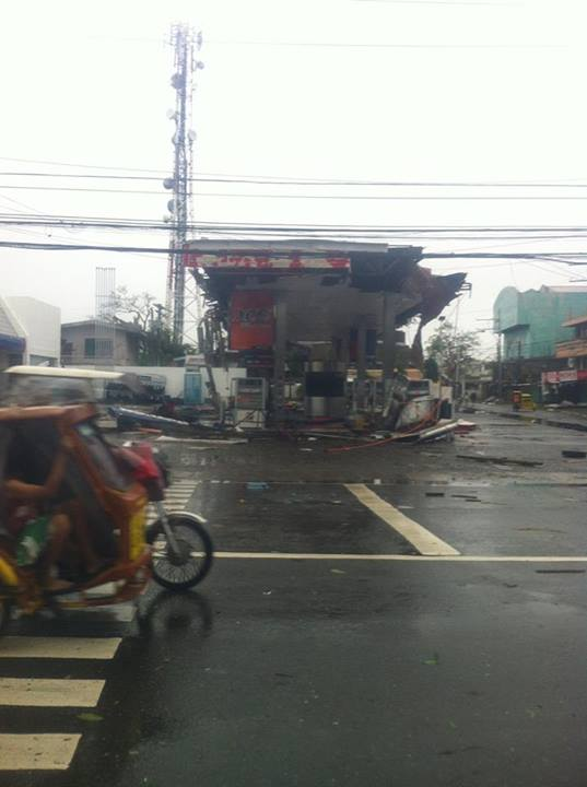 A tricycle passes by a ruined gas station in Roxas City. Photo by Kashmer Diestro, Facebook