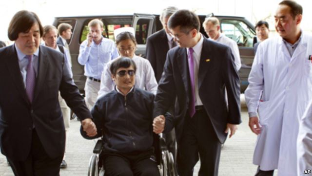 Chen Guangcheng is wheeled into a hospital by Gary Locke, on 2 May 2013. U.S Beijing Embassy Photo.