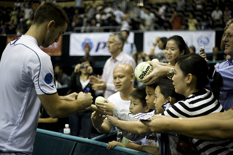 Viktor Troicki signing autographs at PTT Thailand Open 2009; photo courtesy of Government of Thailand, used under Creative Commons 2.0 License.
