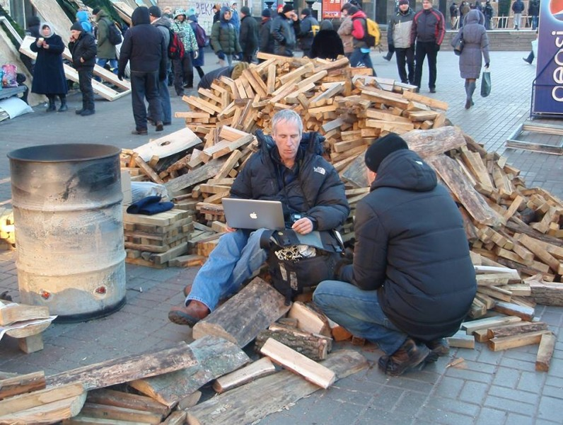 A man holds his laptop while sitting on chopped wood amid protesters in Kyiv, Ukraine. Photo by Dima Kravchuk. Used with permission.