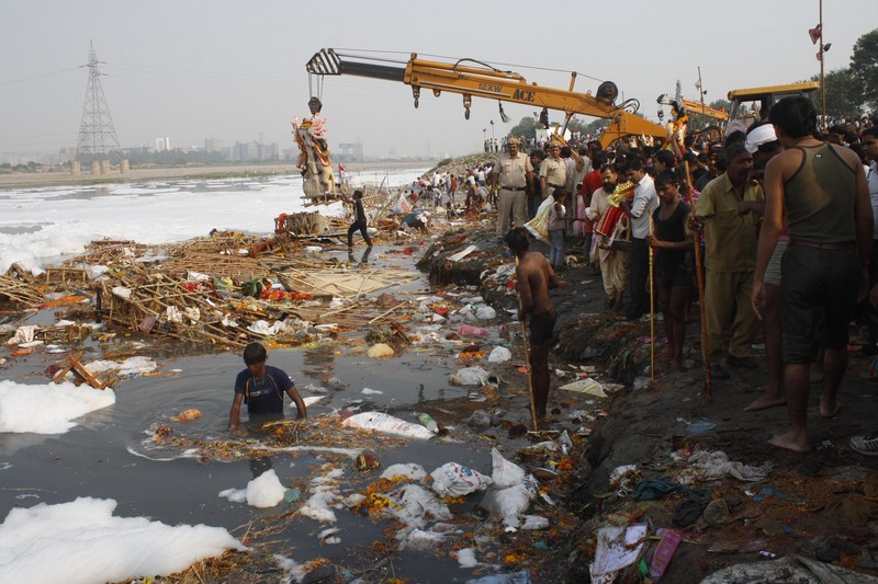 Devotees gather on the banks of the polluted River Yamuna to immerse idols of Hindu goddess Durga during the Durga Puja festival. Image by Burhaan Kinu. Copyright Demotix (24/10/12)