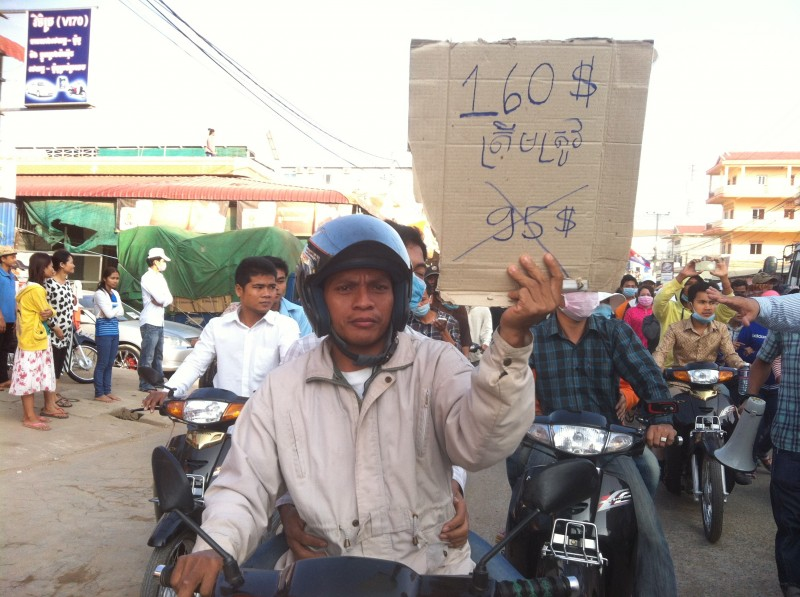 A worker holding a sign calling for a $160 dollar monthly minimum wage. Photo from the blog of Mu Sochua