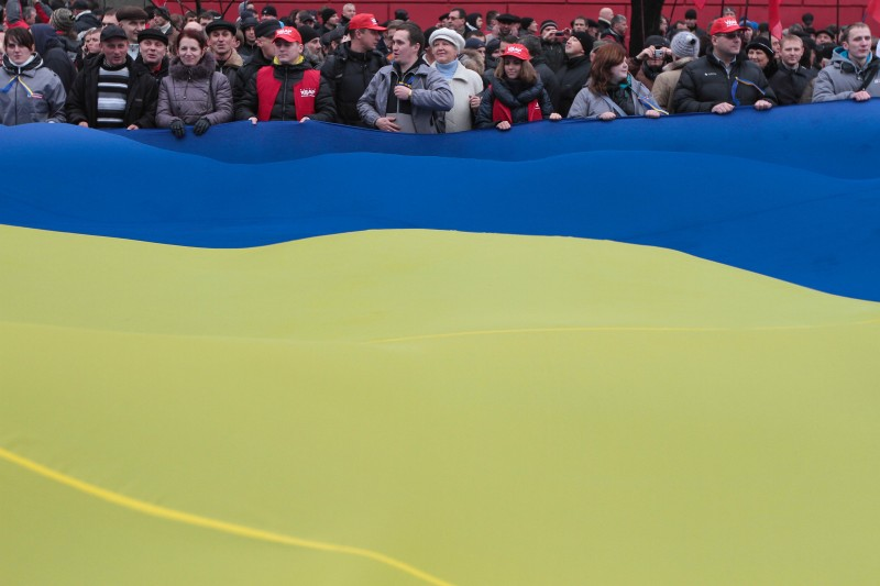 Protesters gathered under flags in Kyiv to demand the Ukrainian government to reverse its policy decision and sign a landmark agreement with the EU; photo by Sergii Kharchenko, courtesy of Demotix, used with permission.