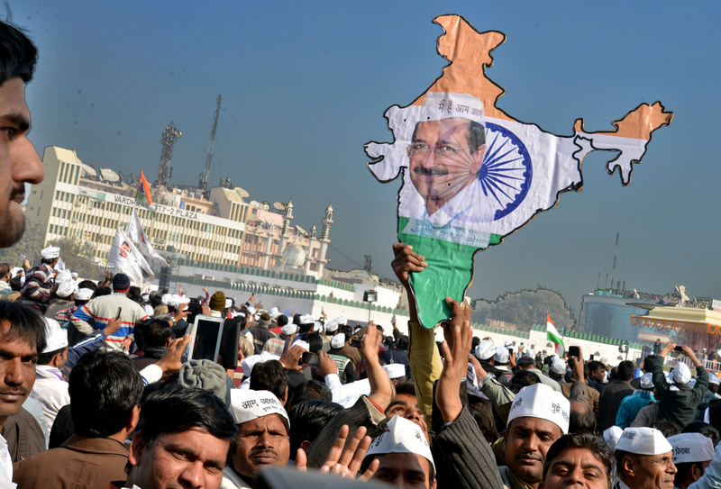 A man holds a placard shaped as India with Arvind Kejriwal picture on it. Image by Rohit Goutam. Copyright Demotix (28/12/2013)