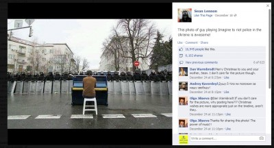 "A screenshot of Sean Lennon's Facebook Mobile uploads. The photo depicts a man playing ""Imagine"" in front of riot police in Kyiv, Ukraine."