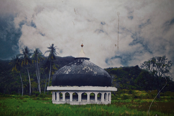 The top of a mosque moved more than a mile by the 2004 Indian Ocean tsunami, as depicted in a poster displayed at the Aceh Tsunami Museum, Banda Aceh, Indonesia. Photo by Ivan Sigal, 2012.