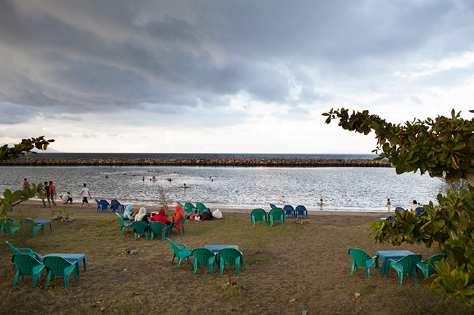 Women sitting by a seawall in Banda Aceh, Indonesia. Photo by Ivan Sigal, 2012.