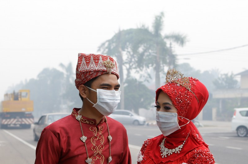 A Malay couple wears a face mask while celebrating their wedding day during haze in Muar, in Malaysia's southern state of Johor bordering Singapore. Photo by Lens Hitam, Copyright @Demotix (6/22/2013)