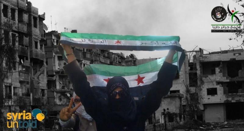 Syrian women raise the Syrian revolution flag. Photo source: Syria Untold