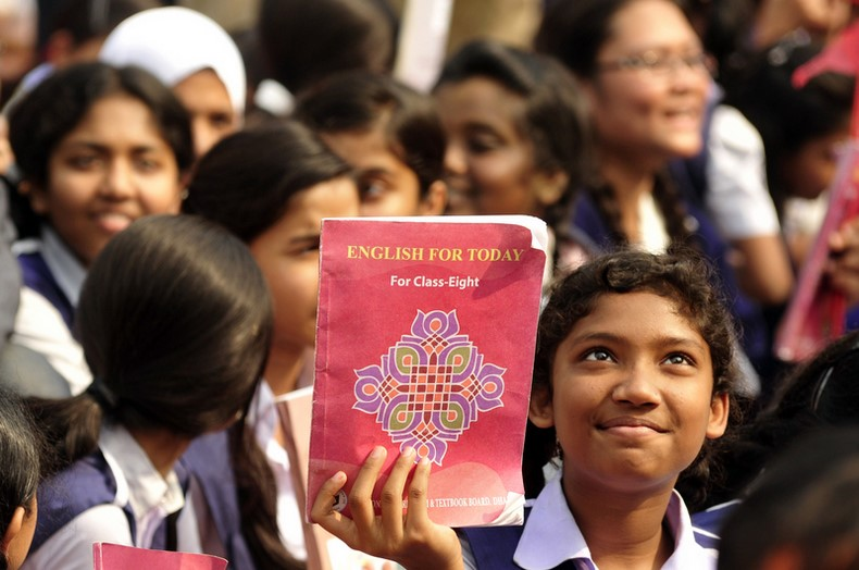 "A Student rises up a textbook during the ""Textbook Festival Day"" program organized by Education Ministry at capital's Government Laboratory School. Image by Firoz Ahmed. Copyright Demotix (2/1/2014)"