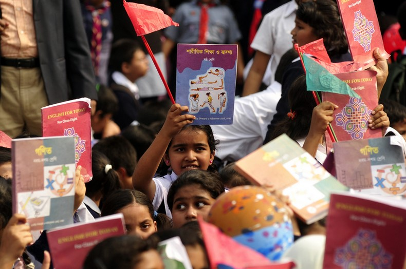 "Students rise up textbooks during the ""Textbook Festival Day"" program organized by Education Ministry at capital's Government Laboratory School. Image by Firoz Ahmed. Copyright Demotix (2/1/2014)"