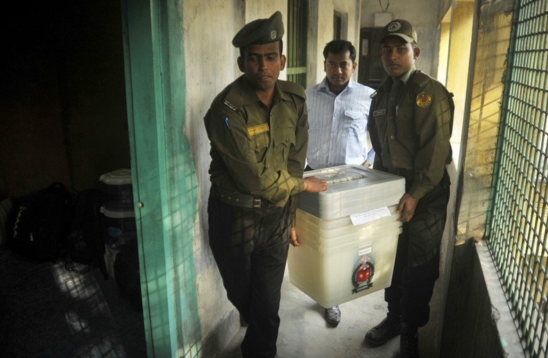 Guards carry ballot boxes and equipment to a polling station that will be used for the 10th parliamentary elections. Image by Naveed Ishtyak. Copyright Demotix (4/1/2014)