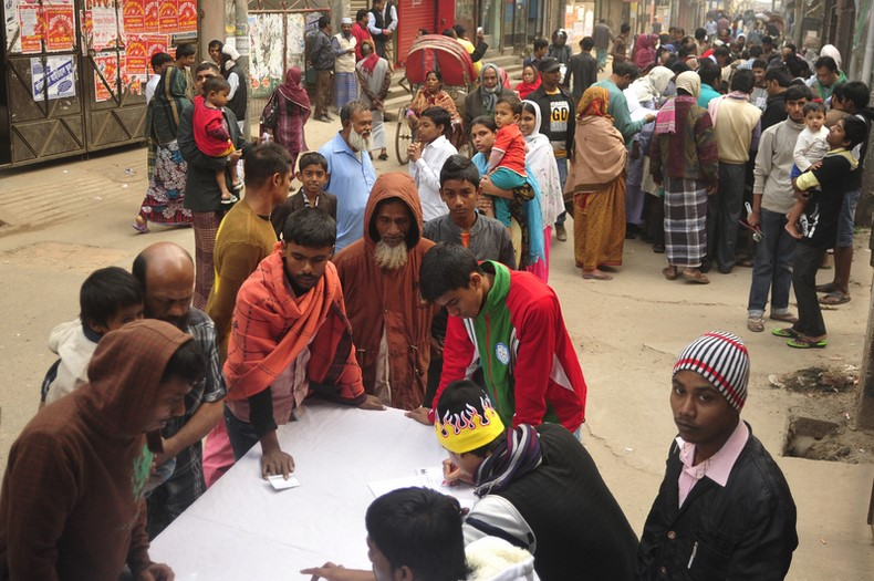 Voters surround a polling agent to collect their voting number in Dhaka-6 constituency during the 10th National Election. Image by Firoz Ahmed. Copyright Demotix (5/1/2014)