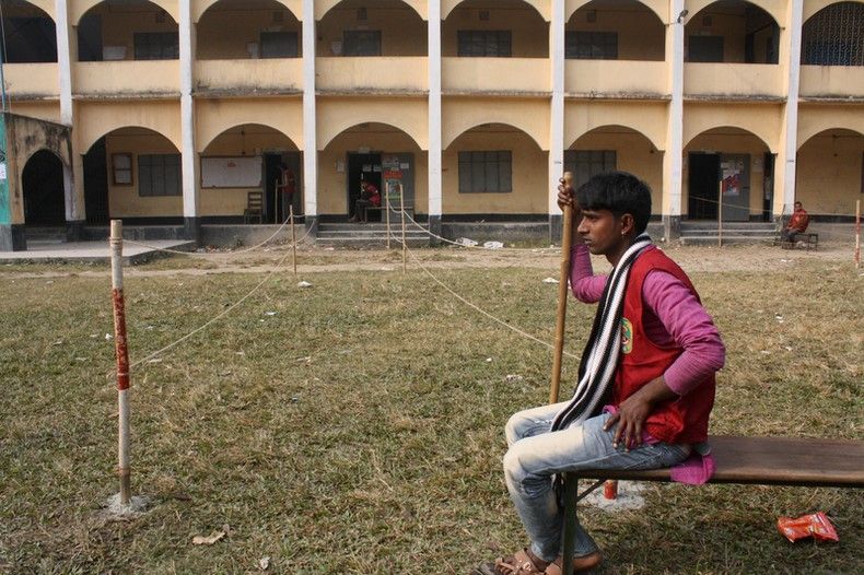 Security parson stand guard in front of vote center at Pilot Girls High School in Nobabgonj near Dhaka. Image by Mamunur Rashid. Copyright Demotix (5/1/2014)