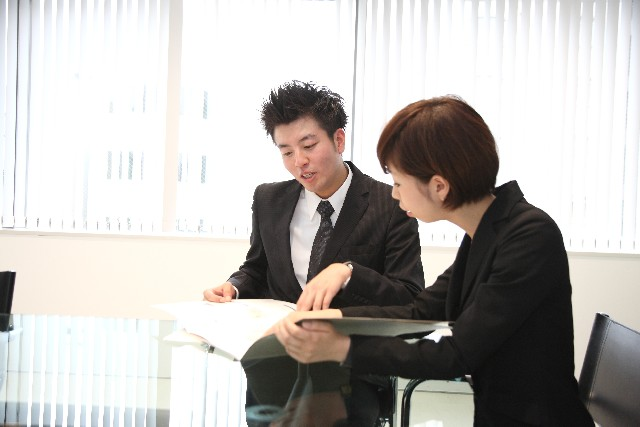 Photo of Japanese male employee and female employee working in office, discussing plans. Rroyalty free photo