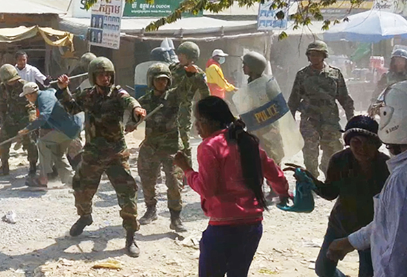 Soldiers threaten a female bystander during a crackdown of the labor protest in Phnom Penh. Photo from Licadho