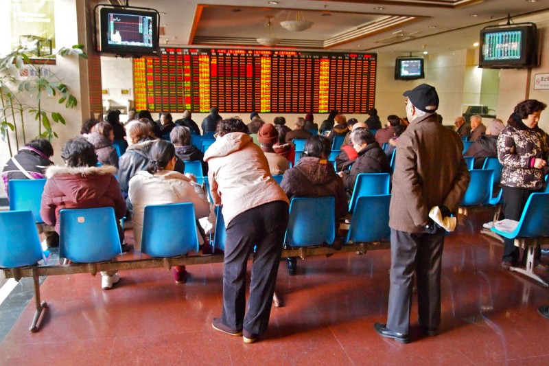 People in the trading hall of a stock and securities exchange company in downtown Shanghai China. Photo by Remko Tanis CC: AT-SA-NC