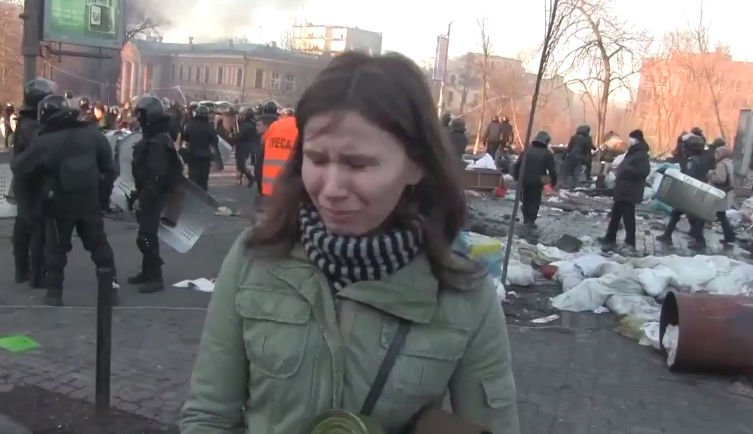 A woman in Kiev reacts to the sight of two dead bodies (protesters killed in the violence). 18 February 2014. Screenshot from YouTube.