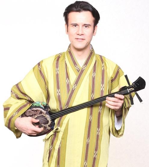 Fija Byron holding sanshin, Okinawan instrument (image used with permmisison)