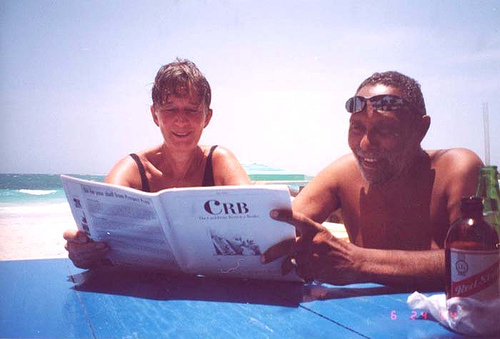 Stuart Hall (R) reading a copy of The Caribbean Review of Books at at Hellshire Beach, Jamaica; June 2004.  Photo by Annie Paul.