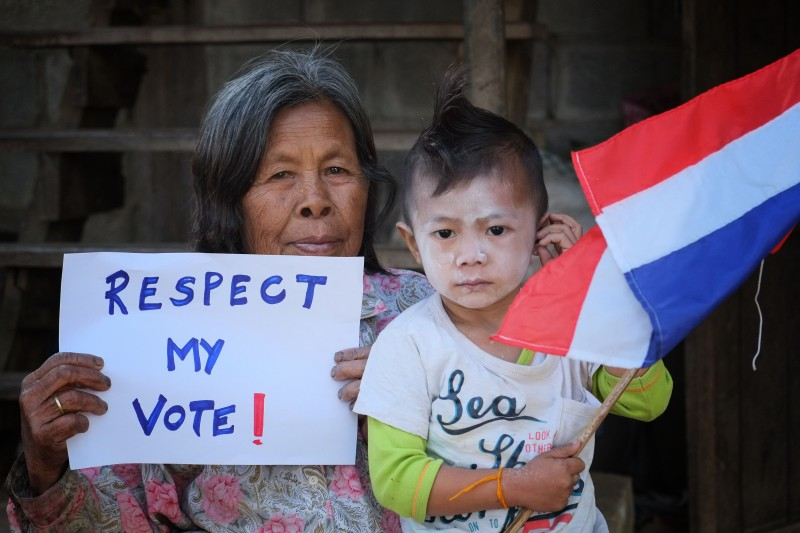 An elderly woman holds a sign that reads 'Respect My Vote' as she poses with her grandchild who holds a Thai national flag. Photo by Matthew Richards, Copyright @Demotix (1/15/2014)