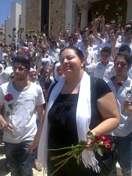 Marcell Shehwaro at the funeral of her mother, who was killed at a Syrian regime forces' checkpoint in June 2012. Fellow activists paid tribute by carrying red roses.