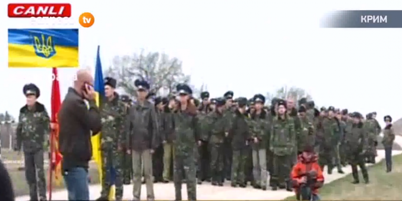 A column of unarmed Ukrainian soldiers confronts a militia checkpoint in the Crimea.