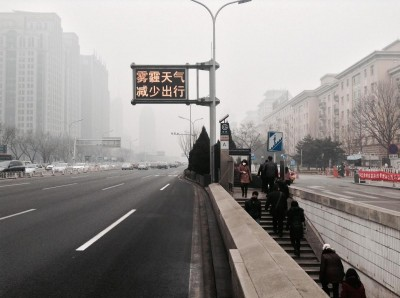 "Photo by Owen. Heavy smog engulfed Beijing in late February 2014. Electric traffic board reads:"" Reduce outdoor activities in smoggy weather."""