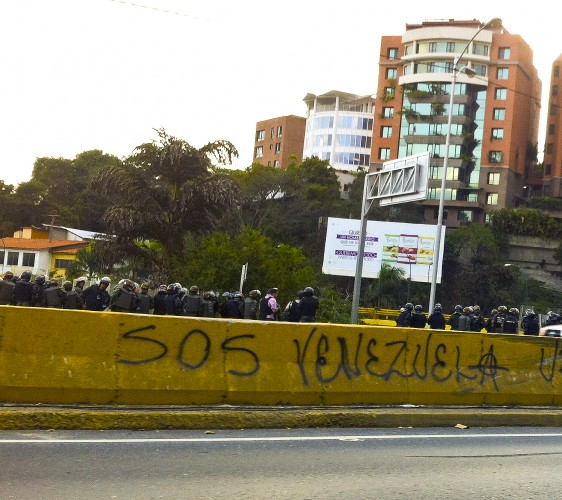 #SOSVenezuela graffiti on the highway and behind the National Bolivarian Guard Soldiers watching the demonstration below. Photo by Kira Kariakin.