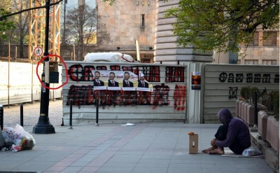Skopje street scene. Foreground share food box and person begging. Background election posters and new government building construction site. Photo by Share food.