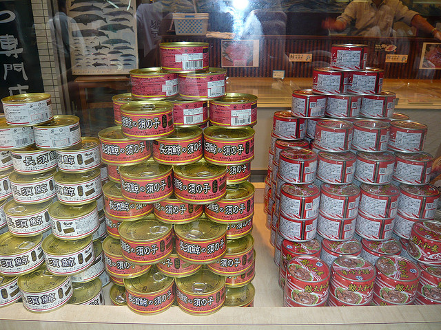 whale meat cans piled up at a store.