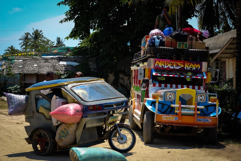 A jeepney beside a trike which is also a popular mode of transportation in the Philippines. Flickr photo by Victor Dumesny (CC License)