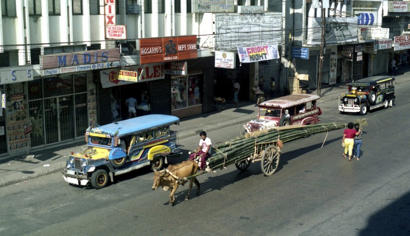 A jeepney beside a bullock with a cart. Flickr photo by 333junction (CC License)