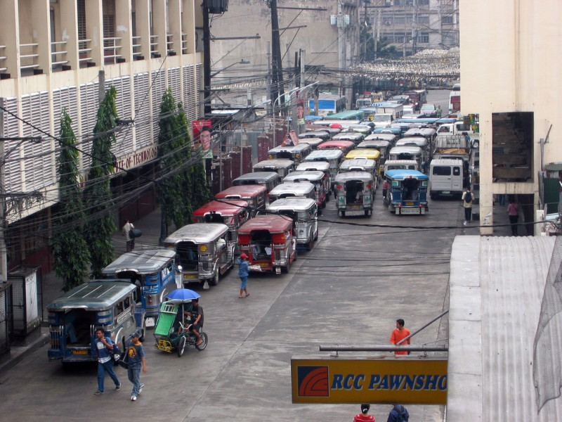 A daily scene in downtown Manila where Jeepneys occupy all the lanes of a street. Flickr photo by Kahunapule Michael J (CC License)
