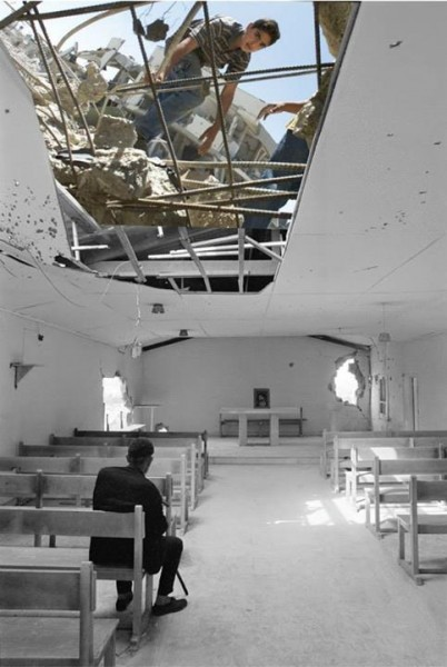 One of the few remaining refugees after the civil strife in Jisr el-Basha camp, passes a quiet moment in the partly damaged Pontifical Mission Church, Lebanon 1976. UNRWA photo archive Palestinian Presidential Headquarters (al-Muqat'a), Ramallah 2002., by Jamal Arouri