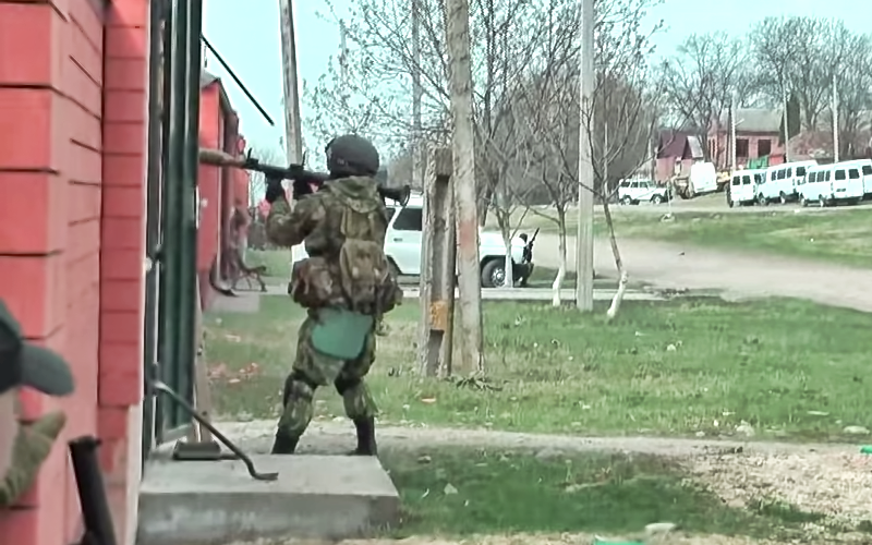 A screenshot from a YouTube video posted from hardingush's account. The special forces soldier is about to fire a grenade launcher during an anti-terrorist operation in the North Caucasus.