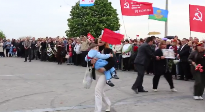 A woman carrying a child charges the stage in disgust, after the Governor speaks ill of the Red Army and ambiguously about Hitler. Kherson, Ukraine. May 9, 2014. YouTube.