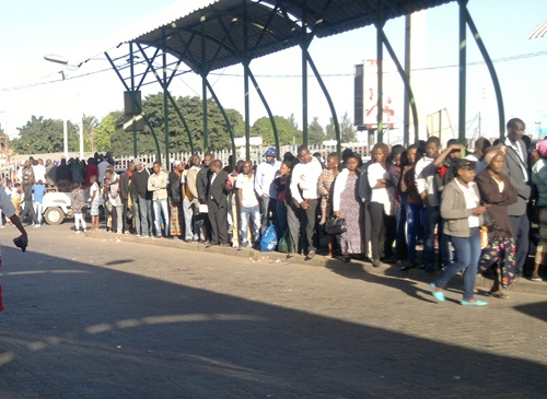 A long line of people wait for transport in Maputo.