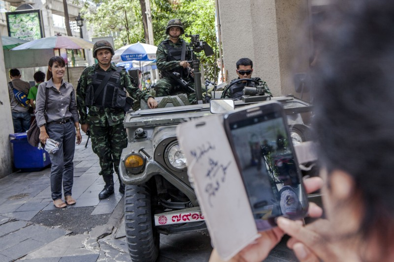 A Bangkok resident poses for a photograph with Thai soldiers. Photo by Vinai Dithajohn, Copyright @Demotix (5/20/2014)