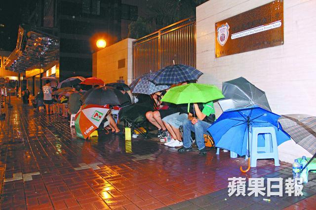 Parents waiting outside an international kindergarten in the rain to hand in application form for their kids. Photo from Apple Daily. Non-commercial use.