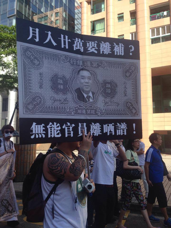 A protest placard showing the Macau Chief Executive's face on a underworld bank note. The slogan on the placard is:  A monthly salary more than 200 thousand dollars [about 25 thousand US dollars] wanted out-going compensation? Impotent officials are out of their mind! Photo from All About Macau Facebook Page